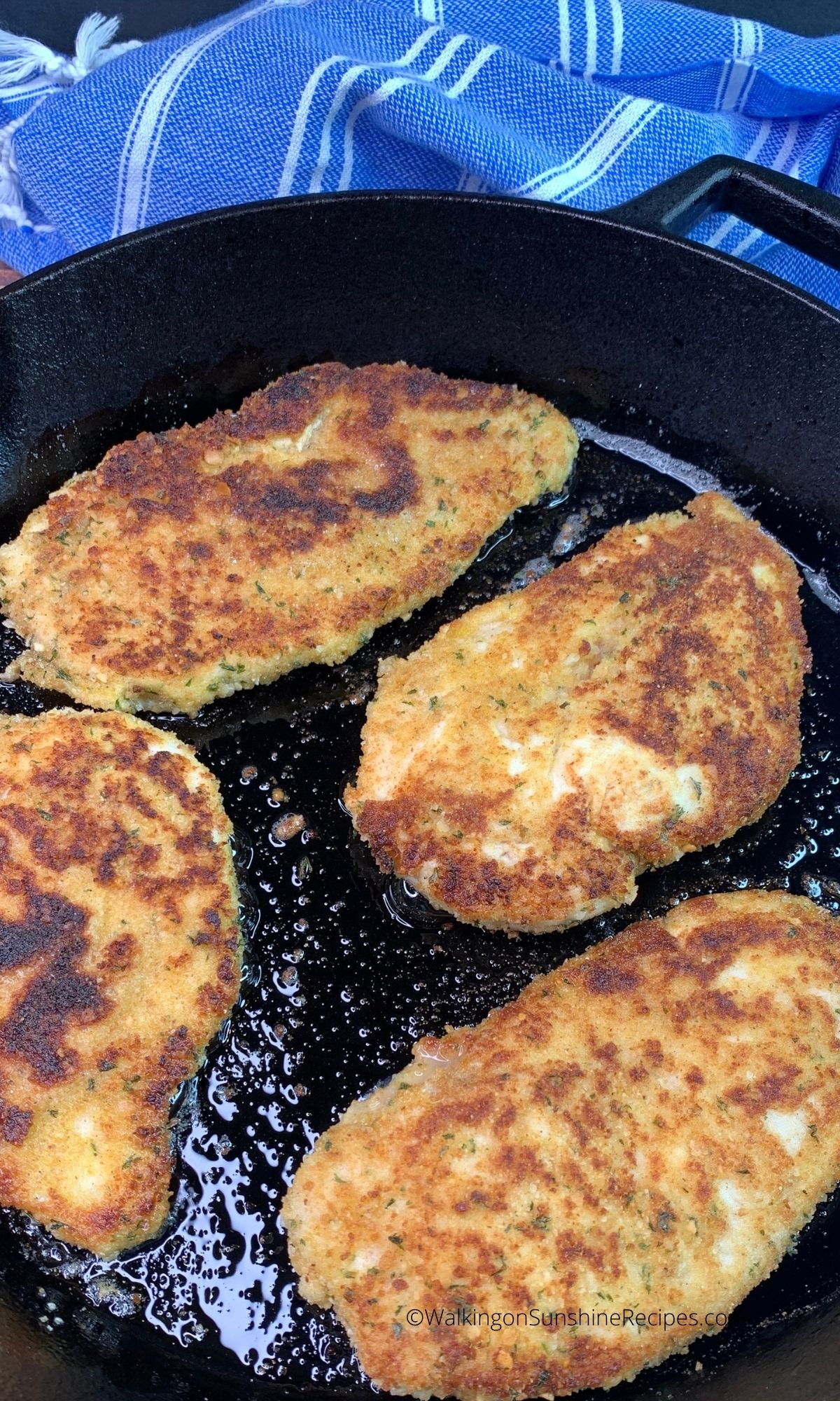 Chicken cutlets in cast iron skillet cooked.