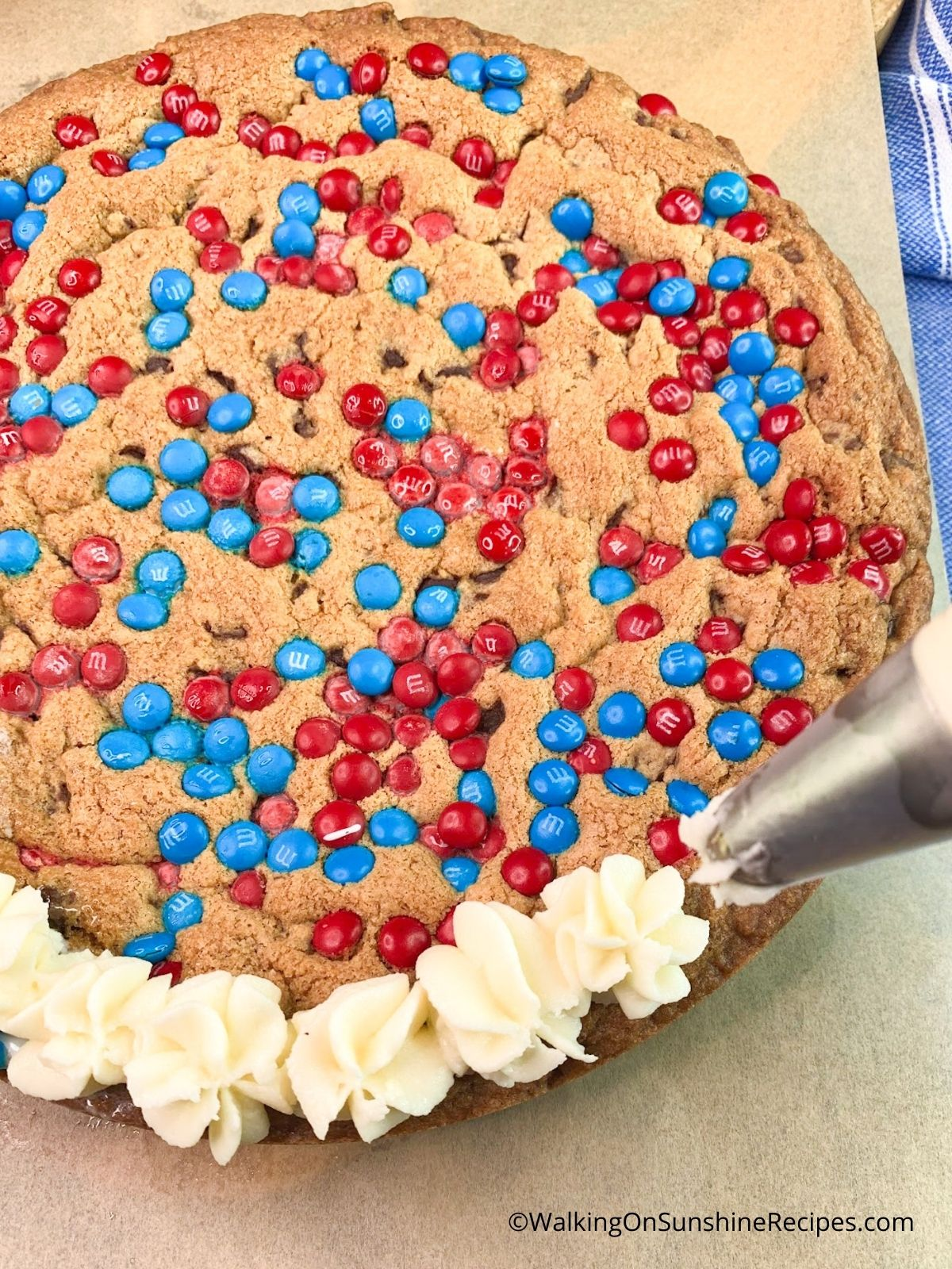 Piping Buttercream Icing around Giant Cookie.