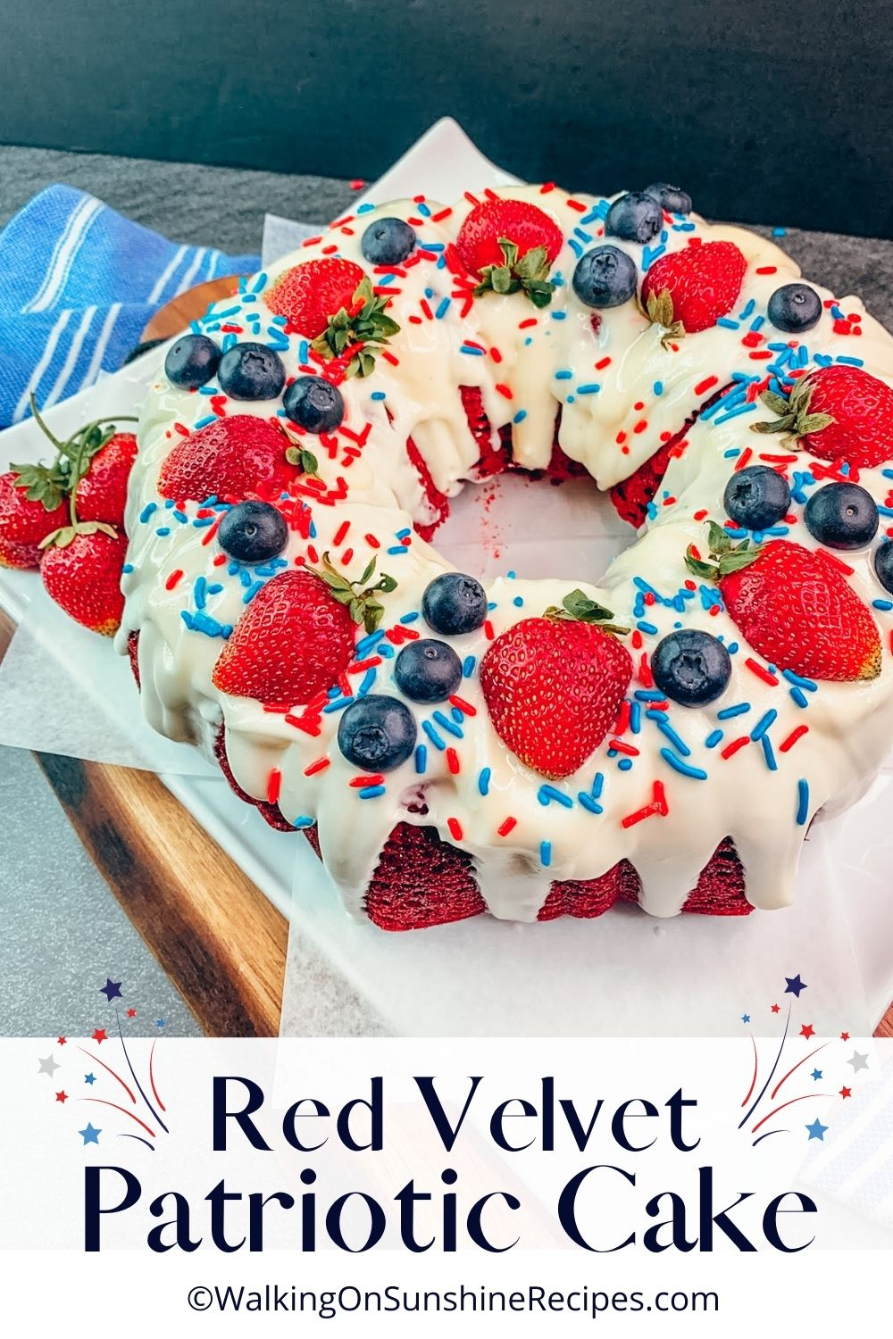 red velvet bundt cake decorated with strawberries, blueberries and sprinkles.