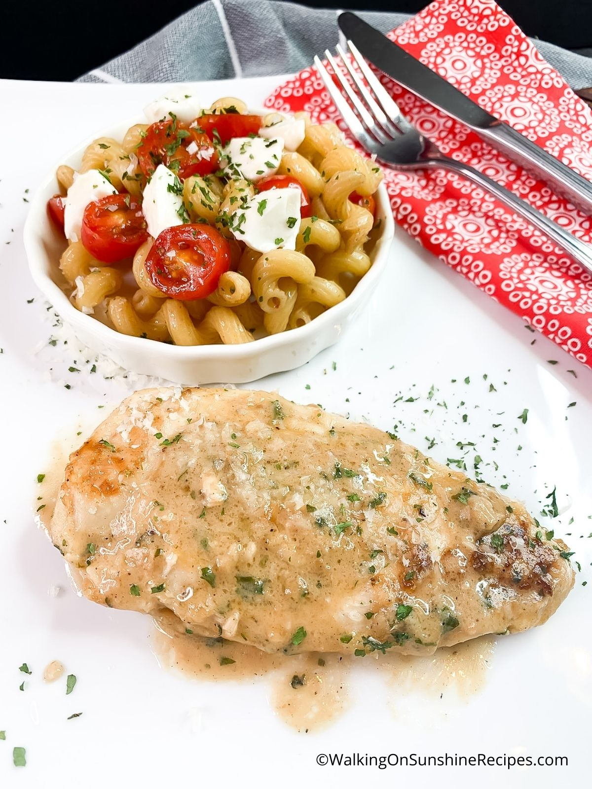 Sauteed chicken cutlets on white plate with pasta and tomatoes in bowl.