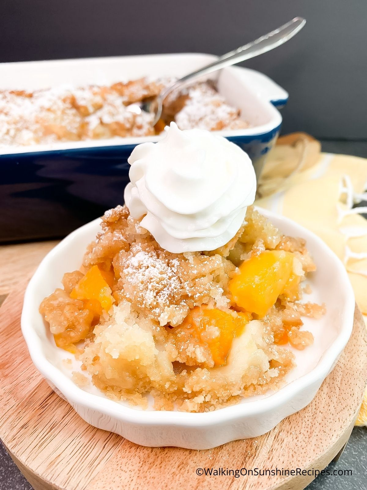 how to serve peach cobbler with whipped cream in small white bowl.