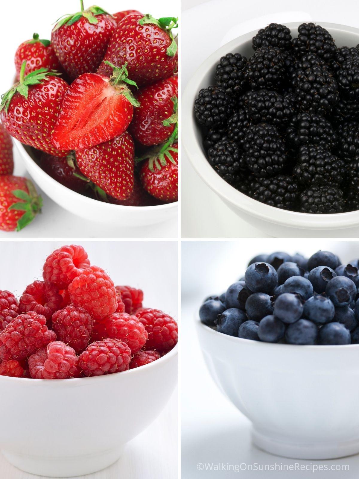 Strawberries, blackberries, raspberries and blueberries in white bowls.