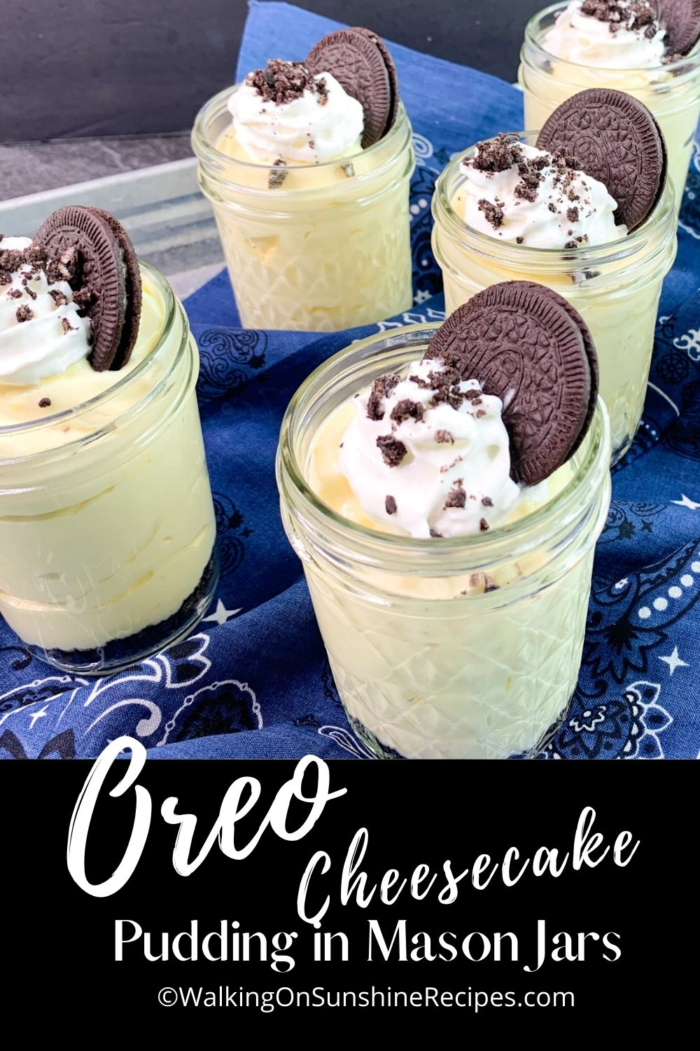 Oreo Cheesecake Pudding in mason jars with whipped cream and an Oreo cookie on top.