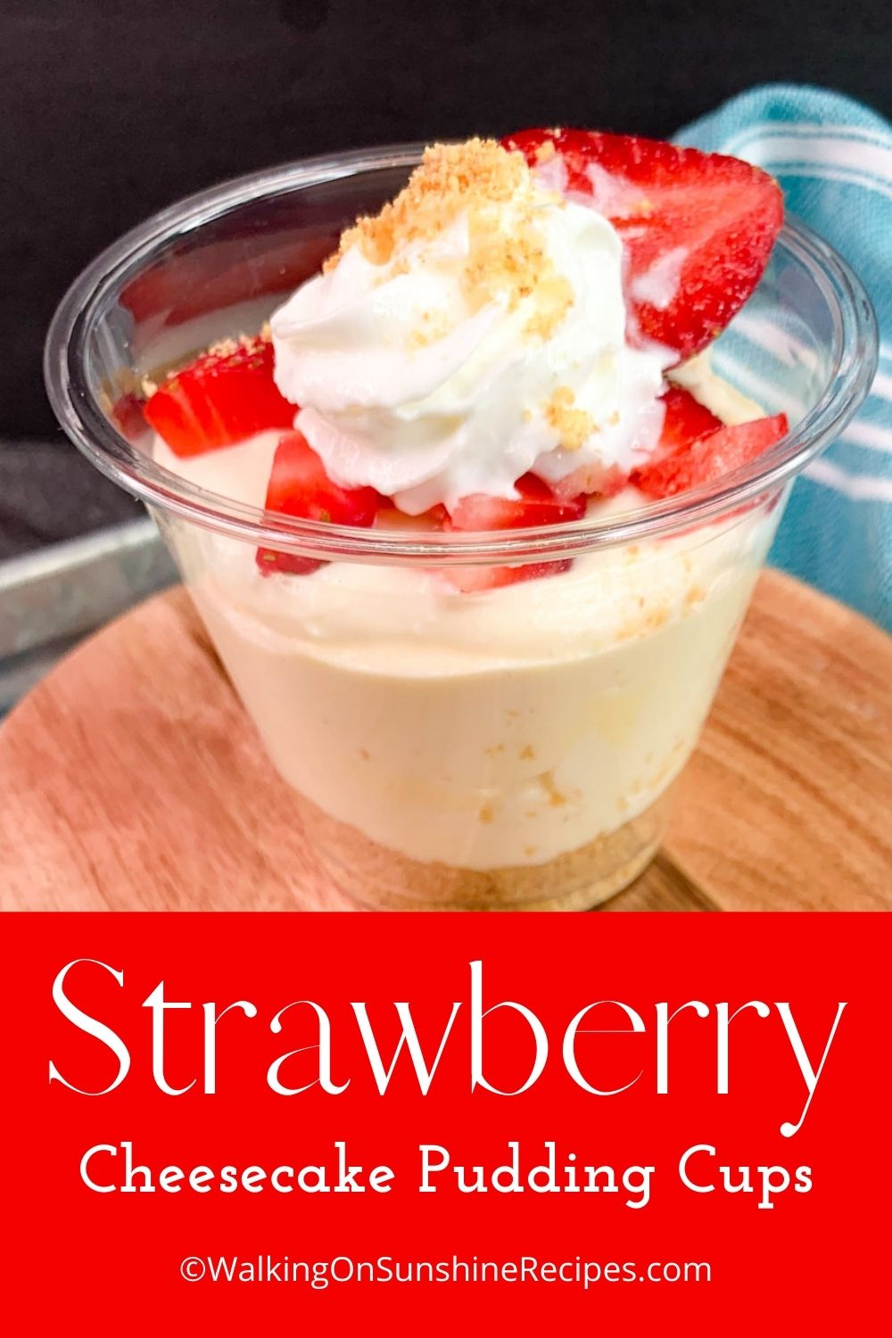 Cheesecake pudding cup topped with strawberries and whipped cream.