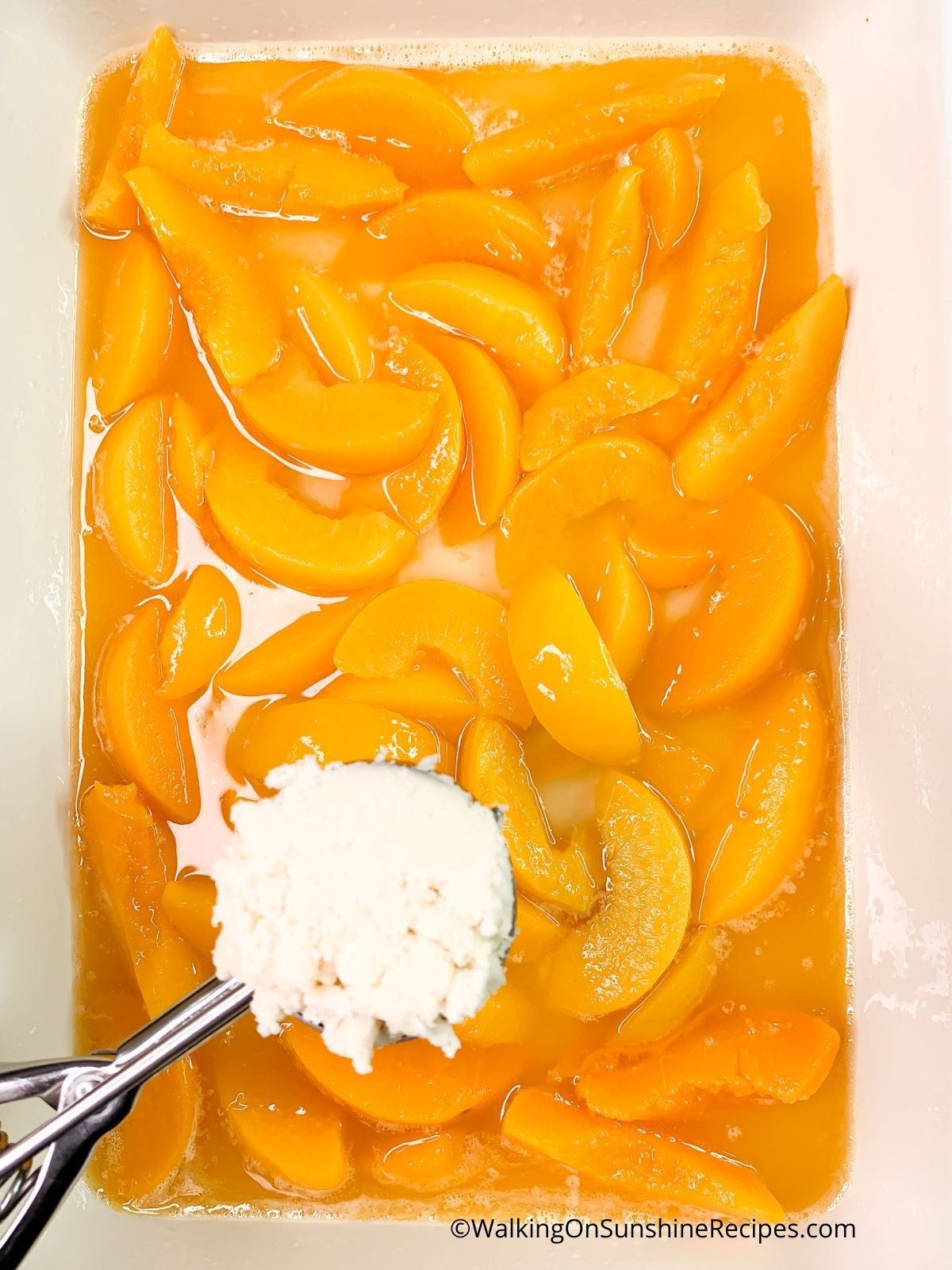 Use a cookie scoop to add white cake mix cobbler topping to canned peaches.