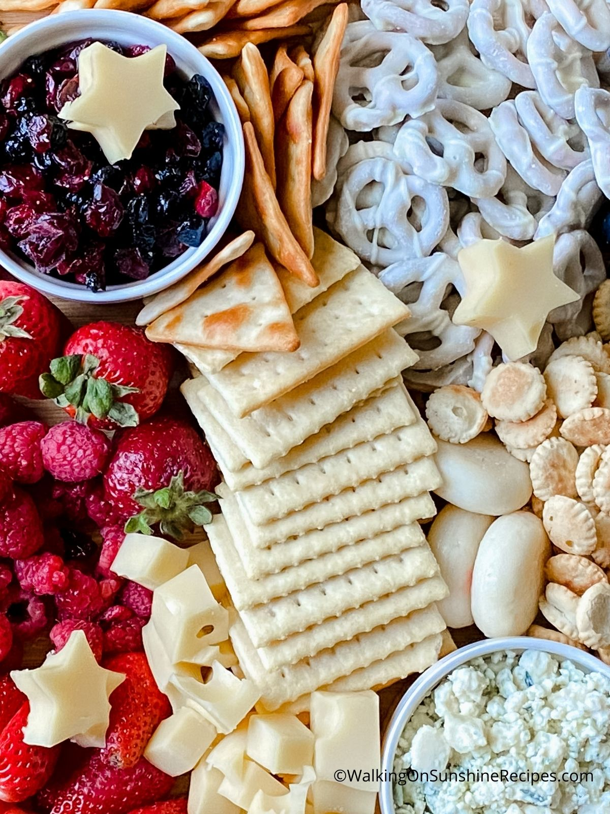 fruit, chocolate covered pretzels, crackers and cheeses on a board.