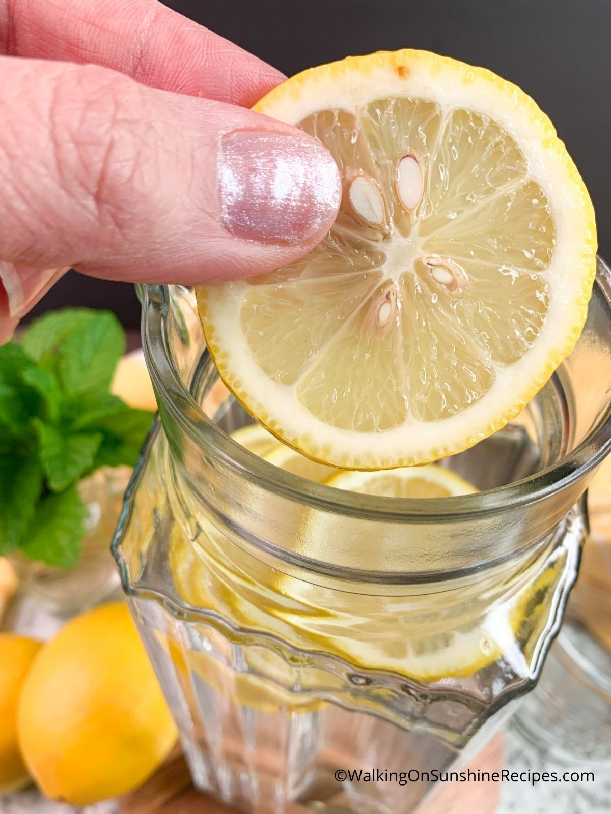 Add lemon slices to pitcher of water.