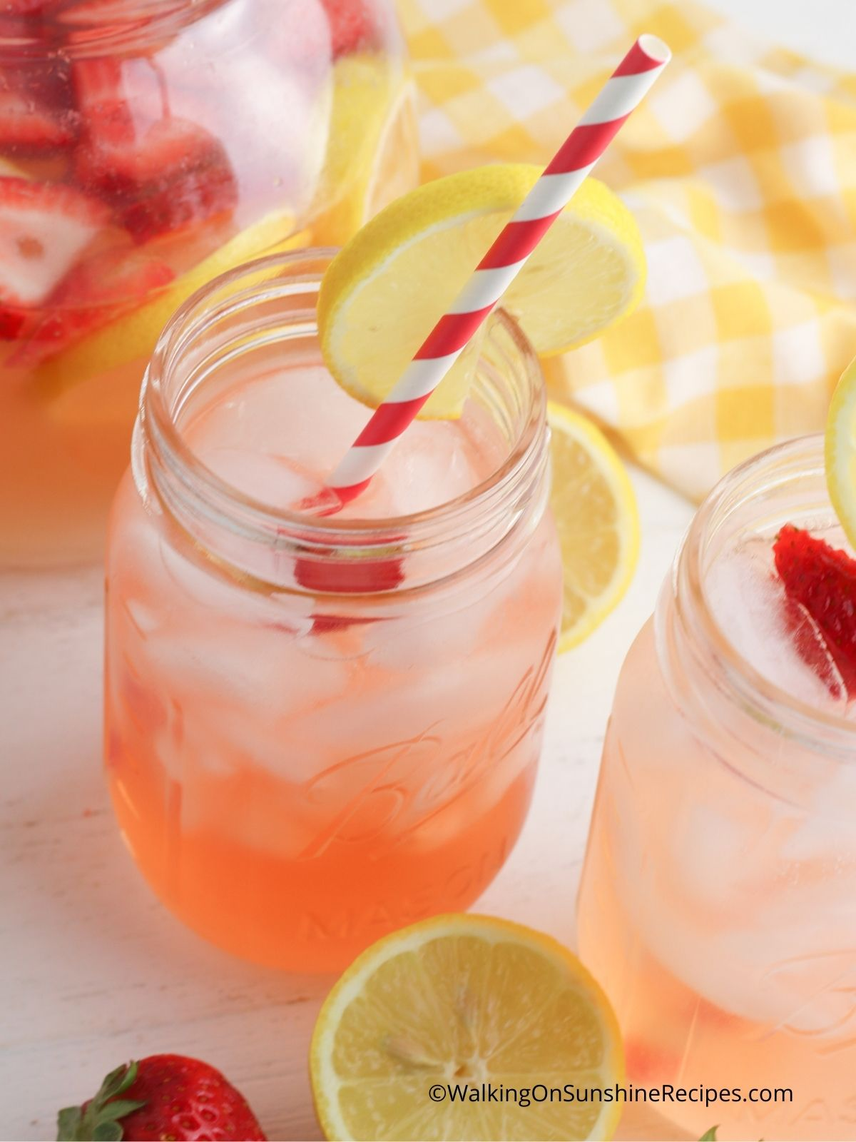 Infused strawberry lemonade in mason jars with red and white striped straws