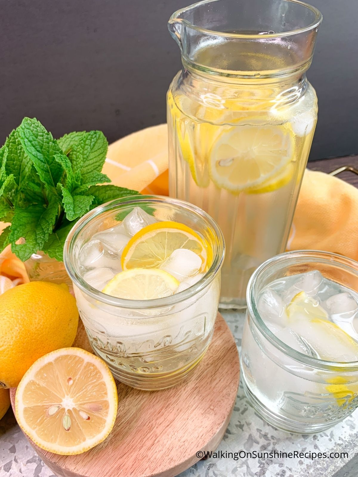 Lemon flavored water in glasses with ice cubes.