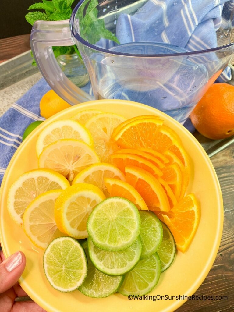 Adding sliced limes, lemons and oranges to water.