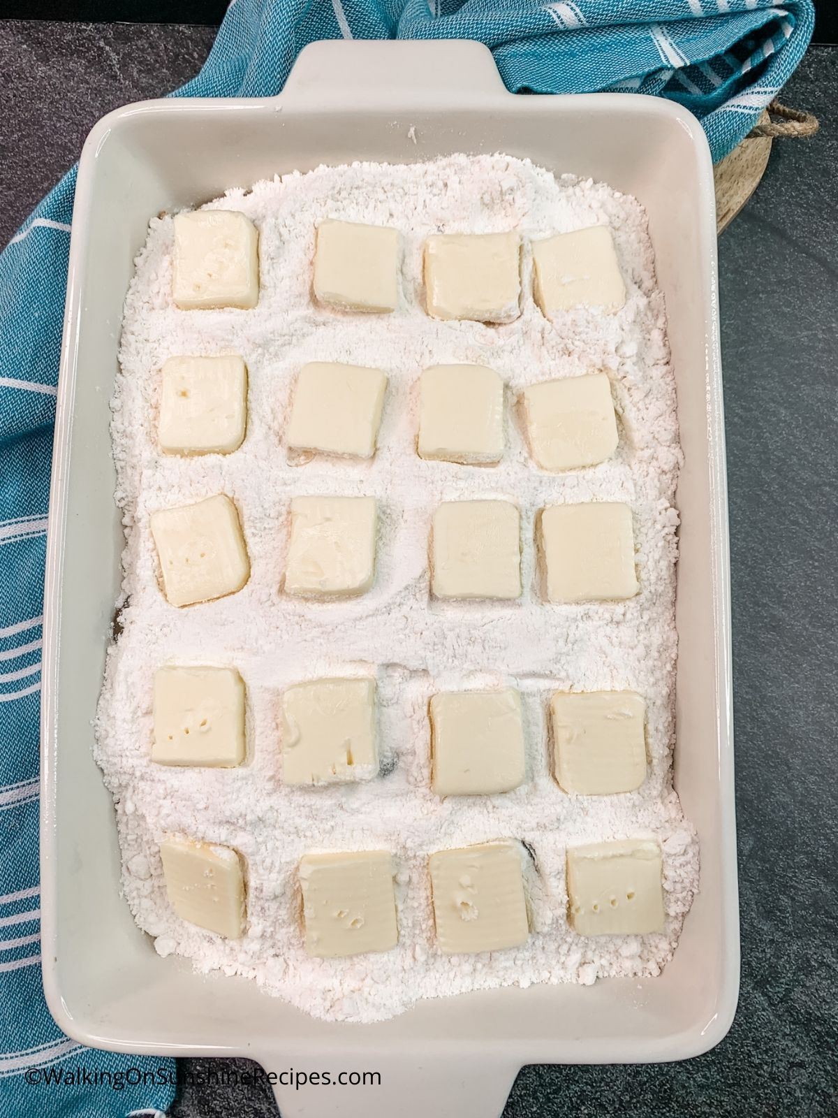 slices of butter on top of vanilla cake mix.