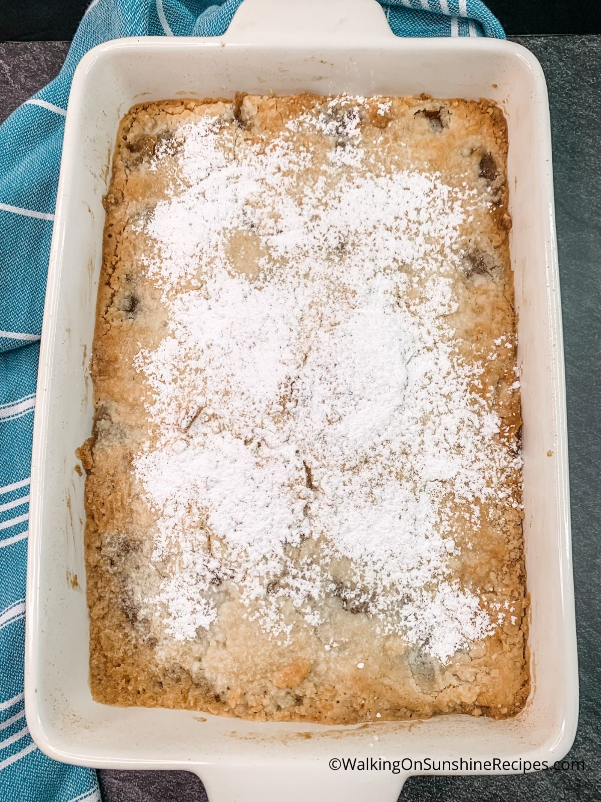 apple dump cake baked with powdered sugar on top.