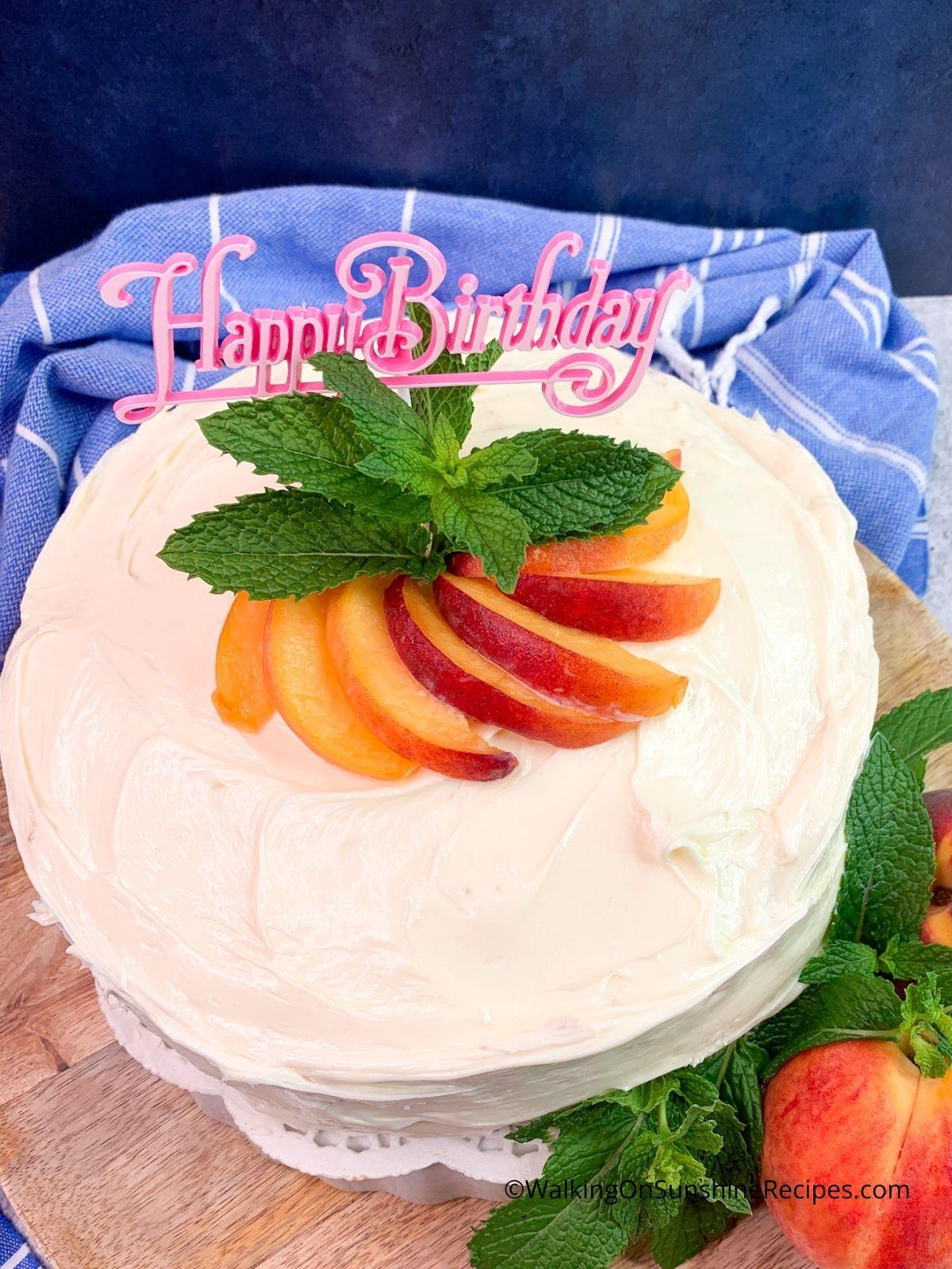 peach birthday cake with fresh peaches.