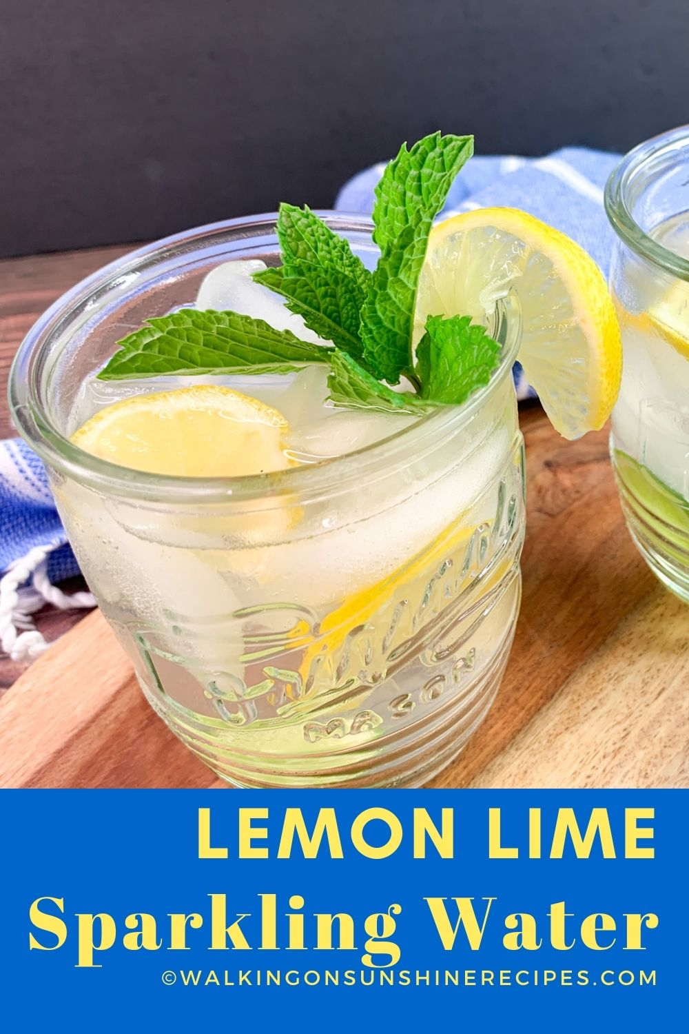 glass of lemon lime water with ice cubes and sprig of mint leaves.