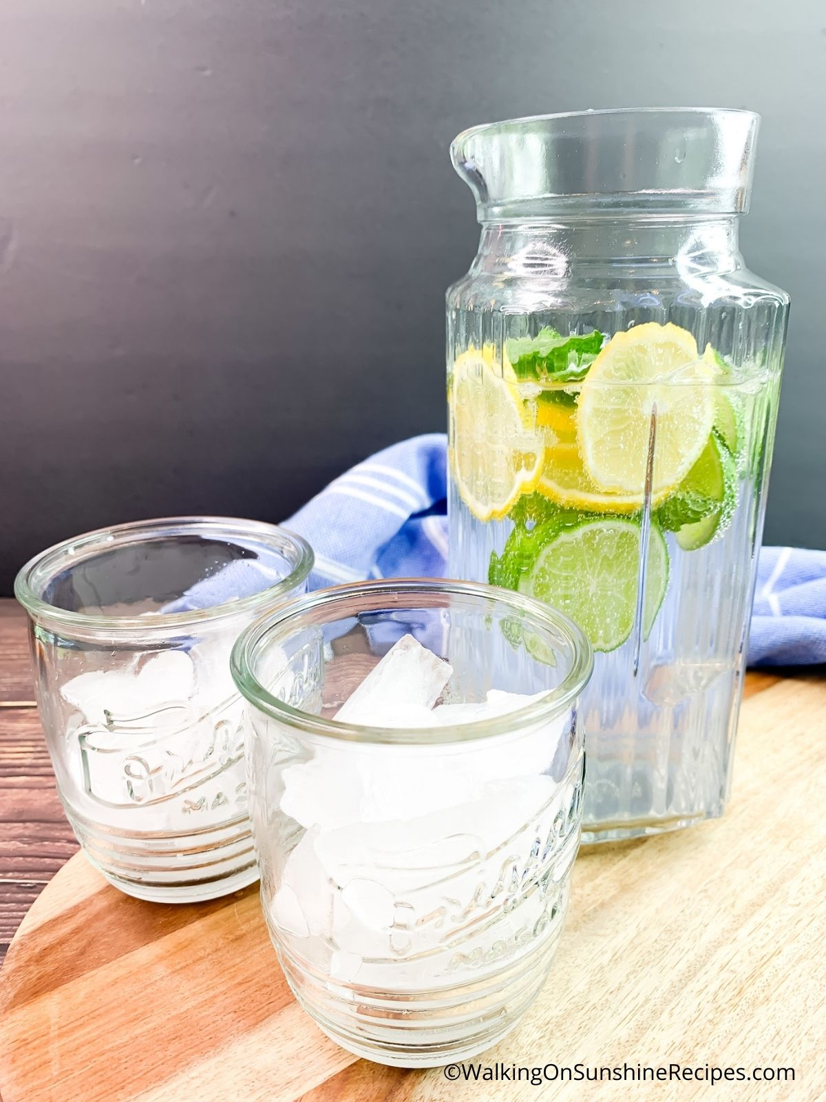 glasses with ice cubes and pitcher of lemon lime water.