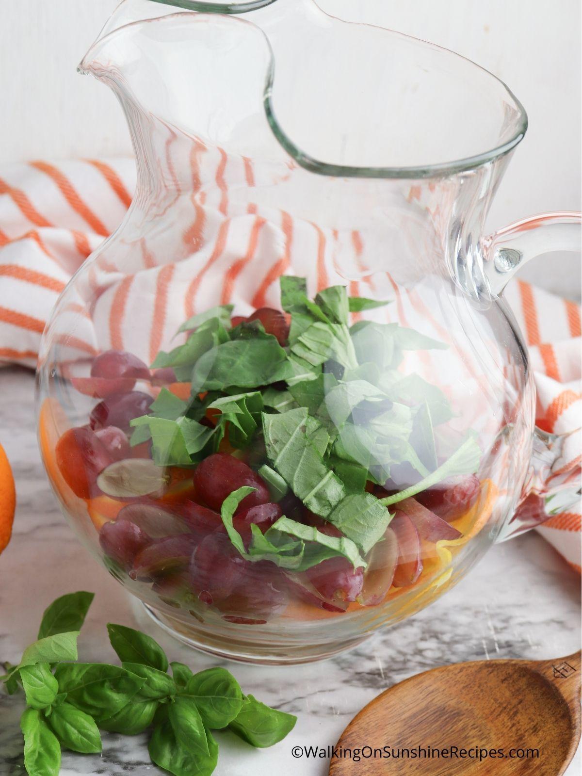 Add fruit, basil to pitcher.